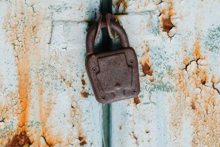 Old padlock on rusty metal painted door