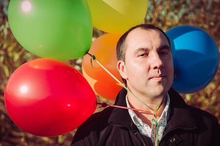 Young man with lot of balloons outdoor