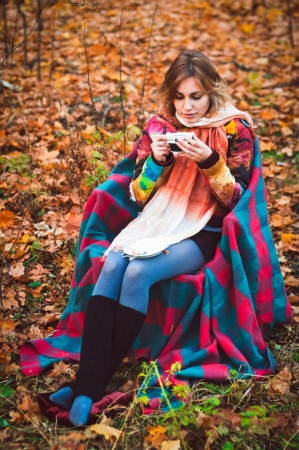 Beautiful girl sitting on armchair in autumn forest with cup in her hands Stock Photo