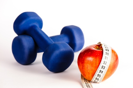 Blue dumbbells and red apple with measure tape isolated on a white background