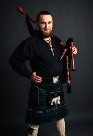 scot: Young man with beard in scottish costume with pipe in his hand. Studio shot Stock Photo