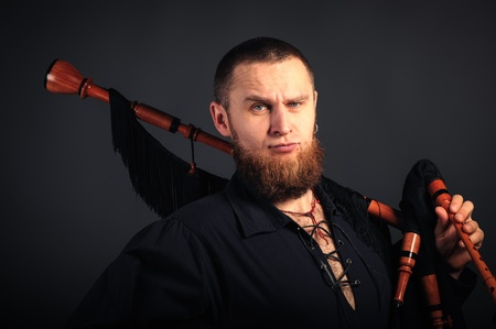 Young man with beard in scottish costume with pipe in his hand. Studio shot Stock Photo