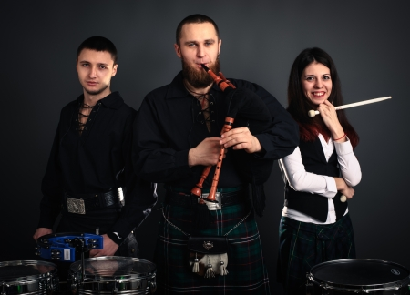 scottish female: Musical band in scottish costumes with pipe and drums. Studio shot
