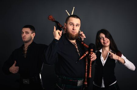 Musical band in scottish costumes with pipe and drums. Studio shot photo