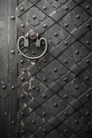 iron nail: Old black door with rivets and flower pattern