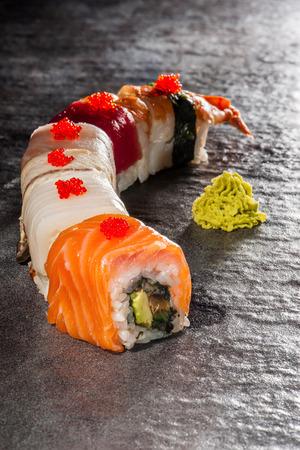 Rainbow Dragon - traditional sushi with salmon, eel, tuna, shrimp, shiitake, perch, avocado and cucumber Stock Photo