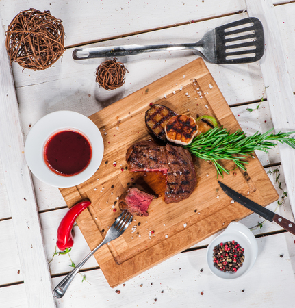 Steak with spices, thyme and chili served on a cutting board Stock Photo