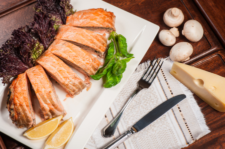 Salmon stuffed with cheese and mushrooms with lettuce and lemon
