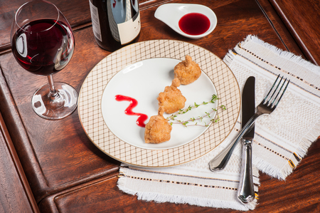 Quail tempura with red sauce on a gilded plate
