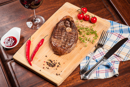 Steak with spices, thyme and chilli served on a cutting board