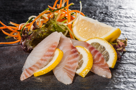 Perch slices with vegetable salad and lemon photo