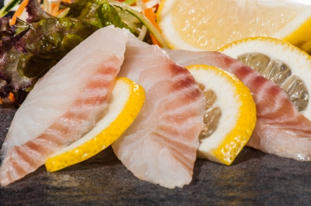 Perch slices with vegetable salad and lemon