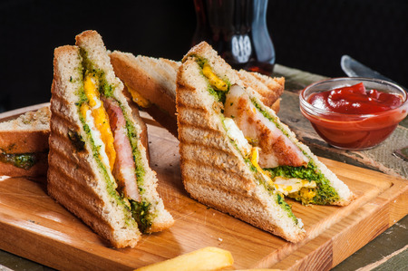 Grilled sandwiches with chicken and egg served with french fries photo