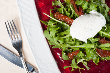 Young beet carpaccio with ricotta and arugula salad photo