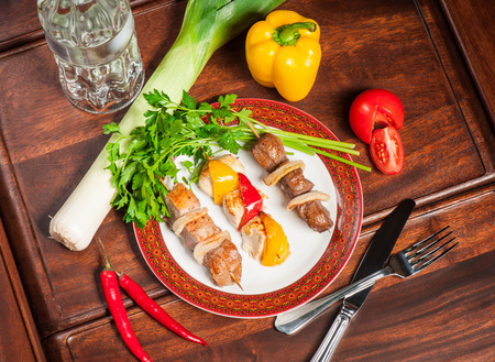 Fried meat with fresh vegetables and bottle of vodka photo