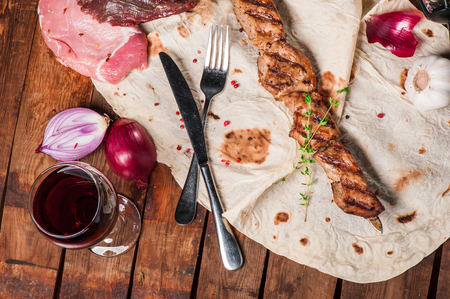 Grilled meat with spices and thyme on skewer lays on pita