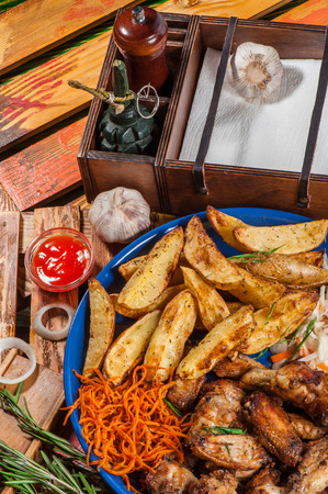 Big plate with fried chicken wings, potato and marinated carrot and cabbage Stock Photo