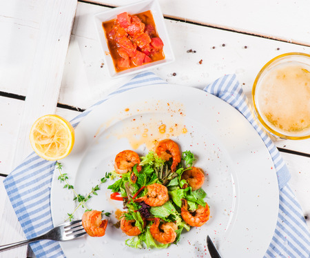 Big shrimps with lettuce leaves and thyme dressing with lemon juice photo