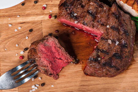 Steak with spices, thyme and chili served on a cutting board photo
