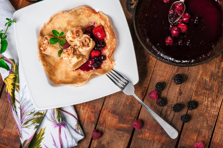 Rolled pancakes with berry jam and fresh mint photo