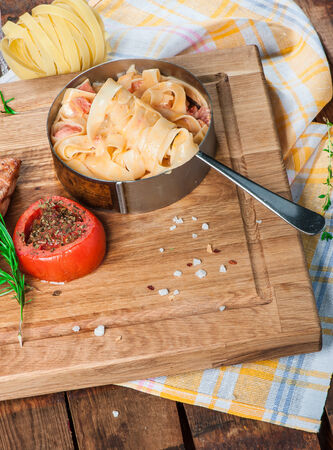 Pasta with parmesan, tomato and grilled salmon on wooden board photo