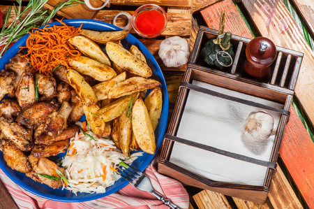 pepper castor: Big plate with fried chicken wings, potato and marinated carrot and cabbage Stock Photo