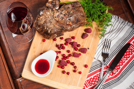 Big piece of fried lamb with sweet berry sauce
