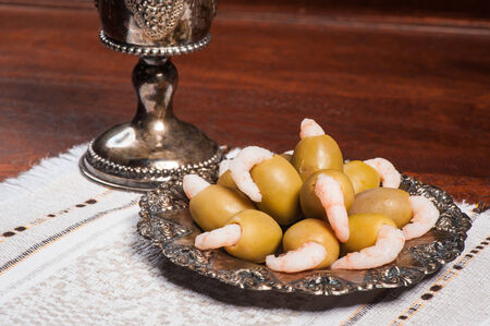 Green olives stuffed with boiled shrimps on silver plate