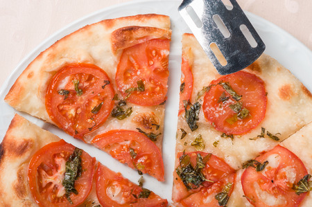 Focaccia with tomatoes, garlic and other spices Stock Photo