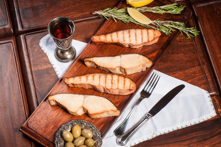 Four pieces of grilled salmon and sturgeon with olives