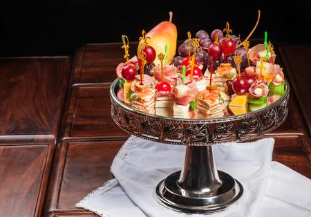 Various kinds of canapes with cheese, meat, fish, fruits and vegetables