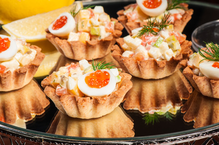 Tartlets stuffed with smoked salmon, cheese and quail eggs