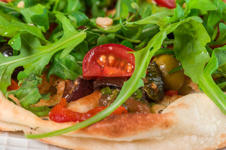 Focaccia with grilled vegetables and arugula on big plate