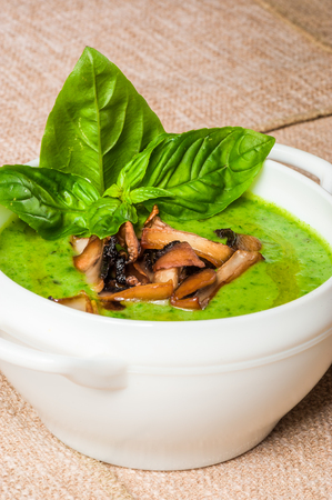 Spinach cream-soup with fried mushrooms and fresh basil