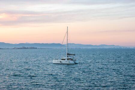 The catamaran against the evening sea  mountains Stockfoto