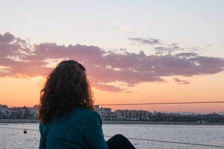 Silhouette of a seated woman looking at sunset Foto de archivo