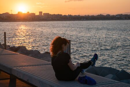 Silhouette of a seated woman looking  sunset