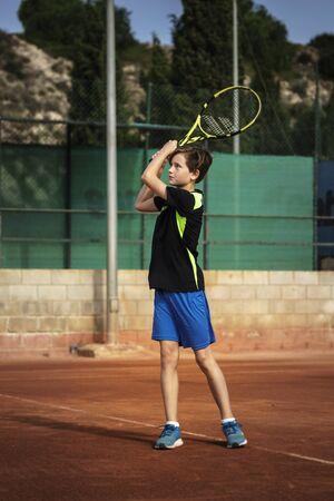 12 years old boy playing tennis, after hiting the ball with two-handed backhand