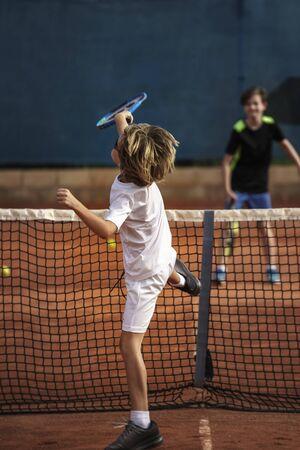 8-letni chłopiec grający w tenisa, po uderzeniu piłką z rozbiciem