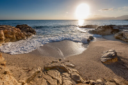 Sunrise over a rocky inlet with gentle surf breaking on the sand as the bright fiery orb of the sun rises slowly in the clear blue summer sky photo