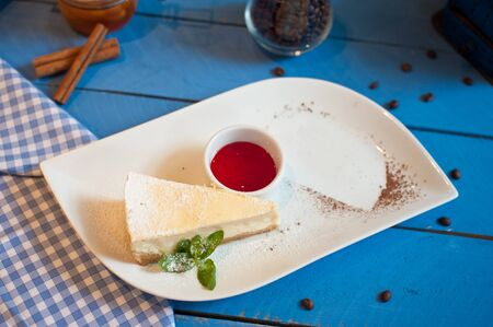 cheesecake on a white plate with a sprig of mint on a blue wooden background raspberry sauce on a white plate