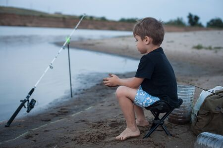 a boy on the Bank of the river is sitting on a chair and fishing. Family vacations, hobbies
