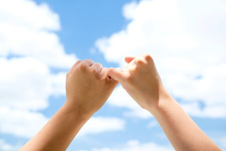 dedo meÑique: El hombre y la mujer que hace una promesa del meñique con el fondo de cielo azul Foto de archivo