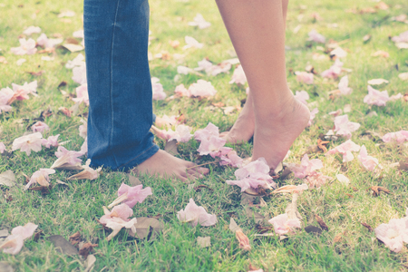 couple nature: vintage tone of : Male and female leg with barefoot in the garden with pink flower on the grounds