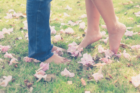 prewedding: vintage tone of : Male and female leg with barefoot in the garden with pink flower on the grounds