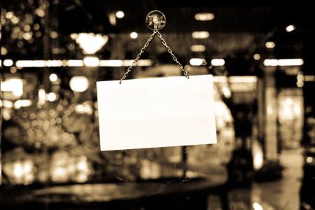 cerrar puerta: Un cartel de cerrado colgando en un escaparate