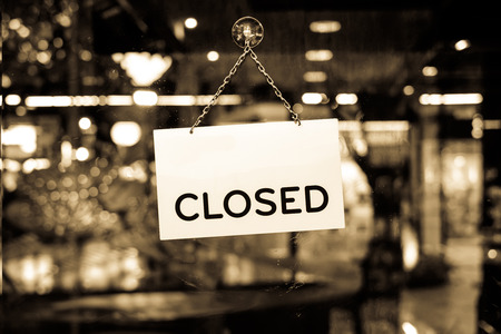 closing: A closed sign hanging in a shop window