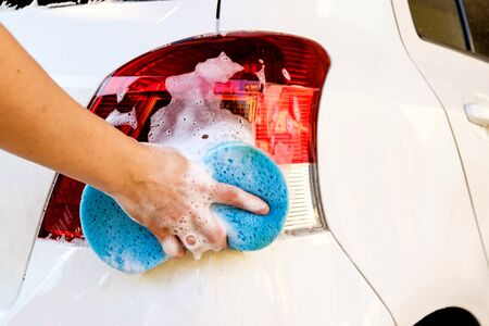 soap sud: close up of hand washing a car with sponge and soap