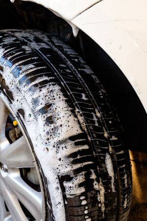 muck: close up washing a car tire with soap