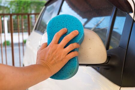 muck: close up of hand washing a car with sponge and soap